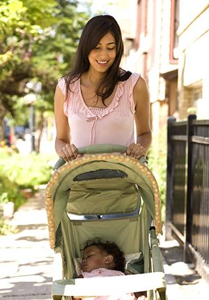 Woman walking baby in stroller.