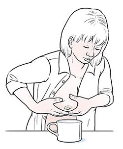 Woman hand-expressing breast milk.