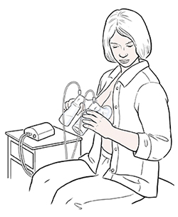 Woman sitting in chair expressing milk from both breasts with electric double breast pump.